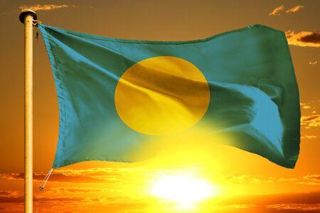 Palau flag weaving on the beautiful orange sunset background