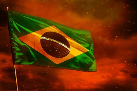 Fluttering Brazil flag on crimson red sky with smoke pillars background. Brazil problems concept.