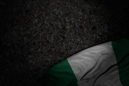 cute dark image of Nigeria flag with large folds on dark asphalt with empty place for text - any holiday flag 3d illustration 写真素材