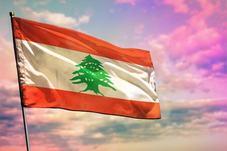 Drapeau du Liban flottant sur fond de ciel nuageux coloré. Concept prospère du Liban.
