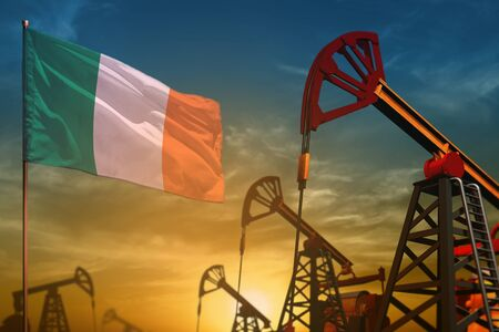 Ireland oil industry concept, industrial illustration. Fluttering Ireland flag and oil wells on the blue and yellow sunset sky background - 3D illustration