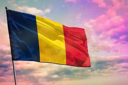 Fluttering Chad flag on colorful cloudy sky background. Chad prospering concept. Stockfoto