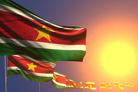 cute national holiday flag 3d illustration  - many Suriname flags on sunset placed diagonal with soft focus and place for your text Banco de Imagens