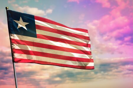 Fluttering Liberia flag on colorful cloudy sky background. Liberia prospering concept.