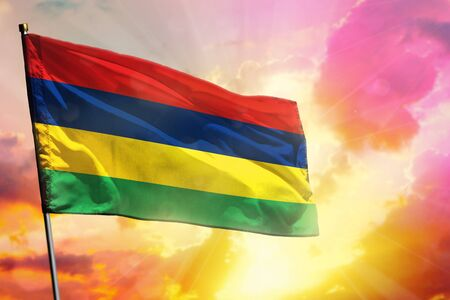 Fluttering Mauritius flag on beautiful colorful sunset or sunrise background. Mauritius success and happiness concept. Imagens
