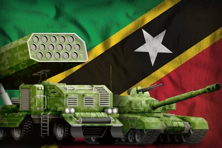 tank and rocket artillery with summer pixel camouflage on the Saint Kitts and Nevis flag background. Saint Kitts and Nevis heavy military armored vehicles concept. 3d Illustration Stok Fotoğraf - 134852335
