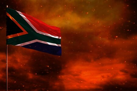 Fluttering South Africa flag mockup with blank space for your data on crimson red sky with smoke pillars background. South Africa problems concept. Banco de Imagens