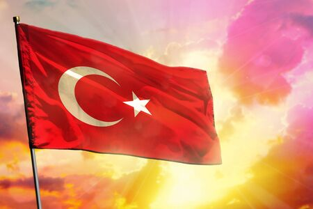 Fluttering Turkey flag on beautiful colorful sunset or sunrise background. Turkey success and happiness concept.