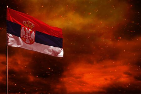 Fluttering Serbia flag mockup with blank space for your data on crimson red sky with smoke pillars background. Serbia problems concept.