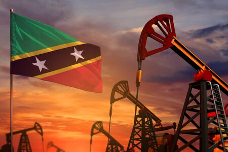 Saint Kitts and Nevis oil industry concept, industrial illustration. Saint Kitts and Nevis flag and oil wells and the red and blue sunset or sunrise sky background - 3D illustration