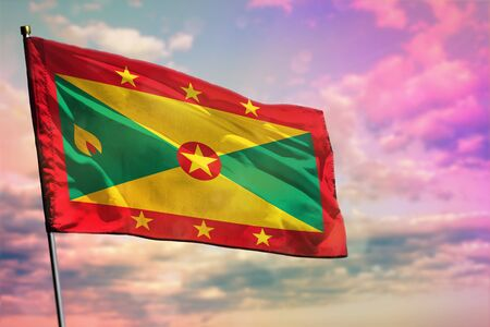 Fluttering Grenada flag on colorful cloudy sky background. Grenada prospering concept.