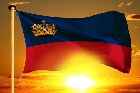 Liechtenstein flag weaving on the beautiful orange sunset background