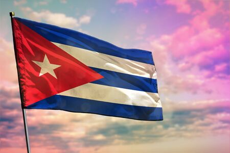 Fluttering Cuba flag on colorful cloudy sky background. Cuba prospering concept.