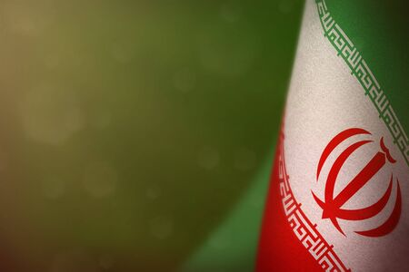 Iran hanging flag for honour of veterans day or memorial day on green dark velvet background. Iran glory to the heroes of war concept.