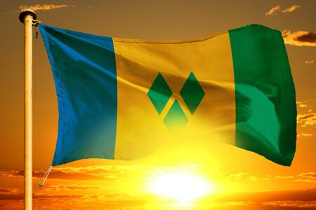 Saint Vincent and the Grenadines flag weaving on the beautiful orange sunset background