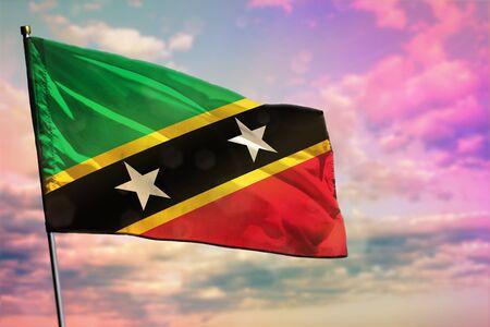 Fluttering Saint Kitts and Nevis flag on colorful cloudy sky background. Saint Kitts and Nevis prospering concept. Stok Fotoğraf