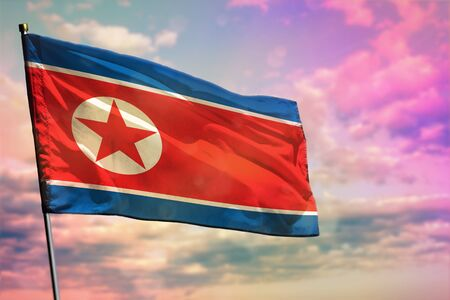 Fluttering Democratic Peoples Republic of Korea (North Korea) flag on colorful cloudy sky background. Democratic Peoples Republic of Korea (North Korea) prospering concept.
