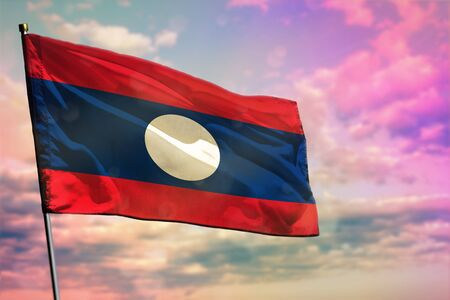Fluttering Lao People Democratic Republic flag on colorful cloudy sky background. Lao People Democratic Republic prospering concept. 写真素材