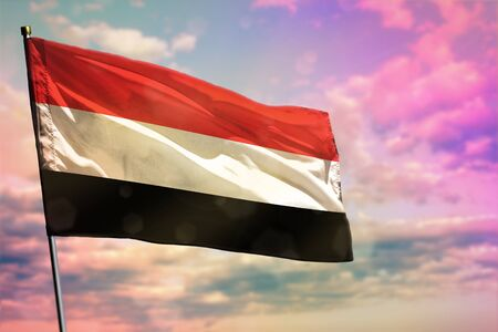 Fluttering Yemen flag on colorful cloudy sky background. Yemen prospering concept. Banco de Imagens