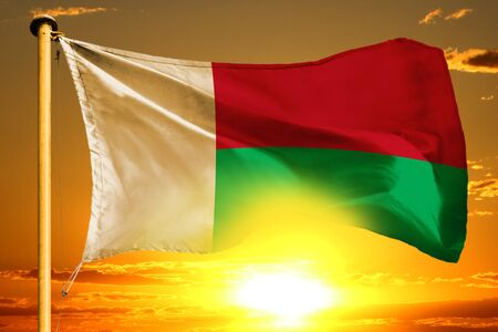 Madagascar flag weaving on the beautiful orange sunset background