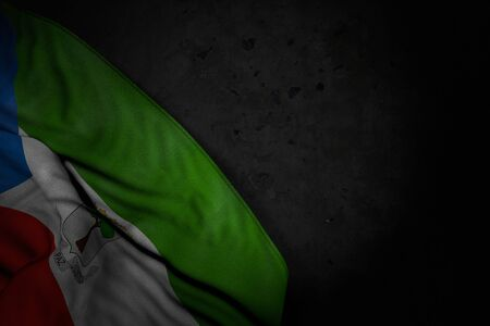 beautiful feast flag 3d illustration - dark picture of Equatorial Guinea flag with big folds on black stone with empty space for text Stock fotó