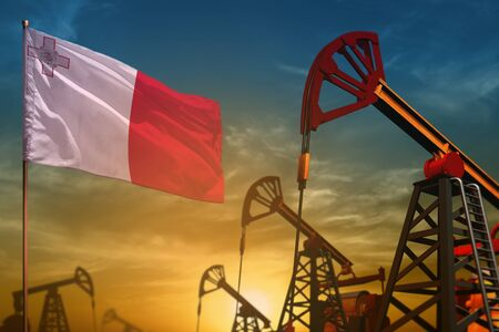 Malta oil industry concept, industrial illustration. Fluttering Malta flag and oil wells on the blue and yellow sunset sky background - 3D illustration