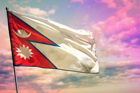 Fluttering Nepal flag on colorful cloudy sky background. Nepal prospering concept.