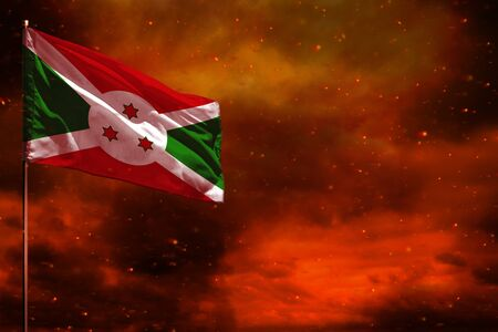 Fluttering Burundi flag mockup with blank space for your data on crimson red sky with smoke pillars background. Burundi problems concept. Stock fotó