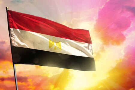 Fluttering Egypt flag on beautiful colorful sunset or sunrise background. Egypt success and happiness concept.