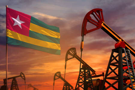 Togo oil industry concept, industrial illustration. Togo flag and oil wells and the red and blue sunset or sunrise sky background - 3D illustration