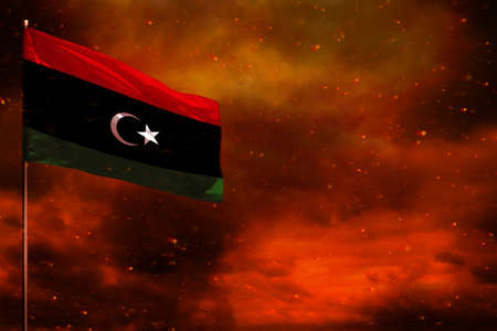 Fluttering Libya flag mockup with blank space for your data on crimson red sky with smoke pillars background. Libya problems concept.