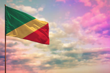 Fluttering Congo flag mockup with the place for your text on colorful cloudy sky background.