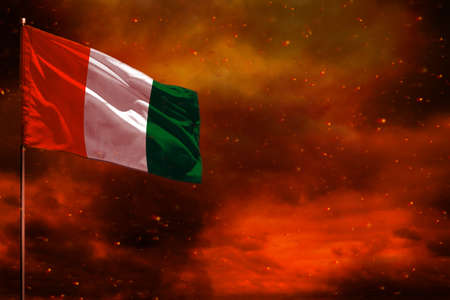 Fluttering Cote d Ivoire flag mockup with blank space for your data on crimson red sky with smoke pillars background. Cote d Ivoire problems concept. Banco de Imagens