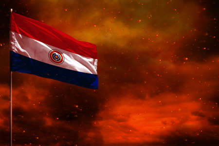 Fluttering Paraguay flag mockup with blank space for your data on crimson red sky with smoke pillars background. Paraguay problems concept.