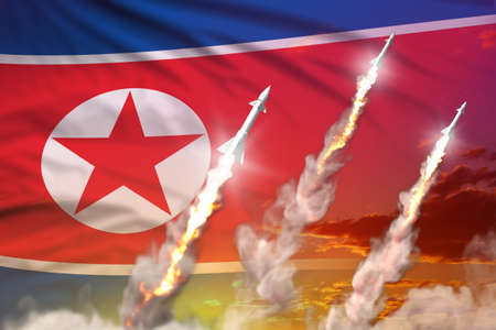 Modern strategic rocket forces concept on sunset background, North Korea ballistic warhead attack - military industrial 3D illustration, nuke with flag 写真素材