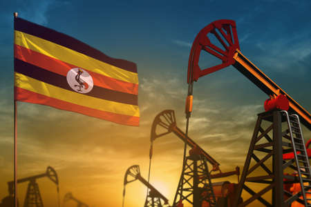 Uganda oil industry concept, industrial illustration. Fluttering Uganda flag and oil wells on the blue and yellow sunset sky background - 3D illustration 写真素材