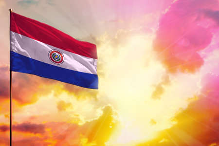 Fluttering Paraguay flag in left top corner mockup with the place for your information on beautiful colorful sunset or sunrise background.