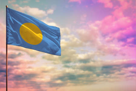 Fluttering Palau flag mockup with the place for your text on colorful cloudy sky background.