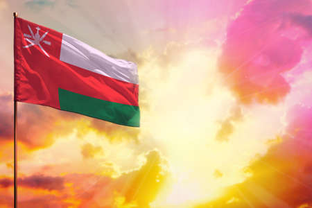 Fluttering Oman flag in left top corner mockup with the place for your information on beautiful colorful sunset or sunrise background.