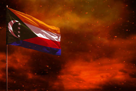 Fluttering Comoros flag mockup with blank space for your data on crimson red sky with smoke pillars background. Comoros problems concept.