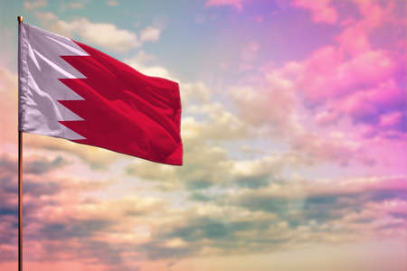 Fluttering Bahrain flag mockup with the place for your text on colorful cloudy sky background. Banque d'images