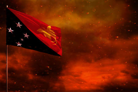 Fluttering Papua New Guinea flag mockup with blank space for your data on crimson red sky with smoke pillars background. Papua New Guinea problems concept.