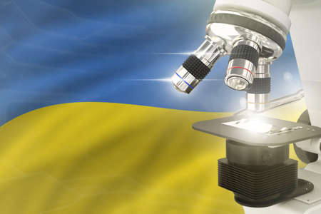 Ukraine science development concept - microscope on flag background. Research in clinical medicine or vaccine 3D illustration of object Imagens