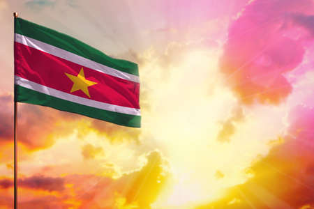 Fluttering Suriname flag in left top corner mockup with the place for your information on beautiful colorful sunset or sunrise background. Imagens