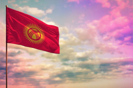 Fluttering Kyrgyzstan flag mockup with the place for your text on colorful cloudy sky background.