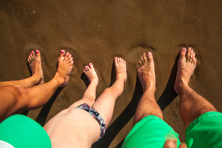 standpoint: Legs of the happy family, father, mother and suns at the sandy beach