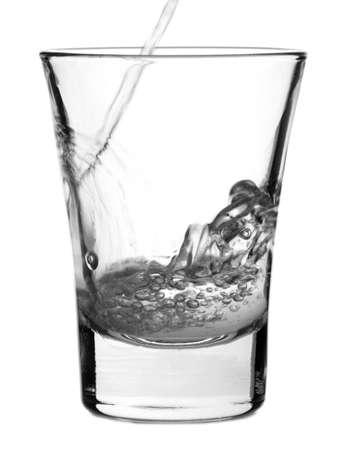distilled: Versando un colpo di vodka a sfondo bianco