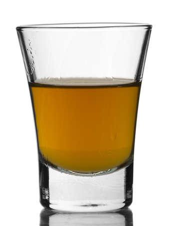 distilled: Un colpo di whisky con riflesso su sfondo bianco