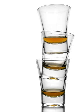 rhum: A pile of three almost empty shots of whisky on white background with reflex Stock Photo