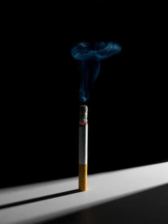habit: A single smoking cigarette standing in a narrow corridor of light. A conceptual image about the smoking habit. Stock Photo